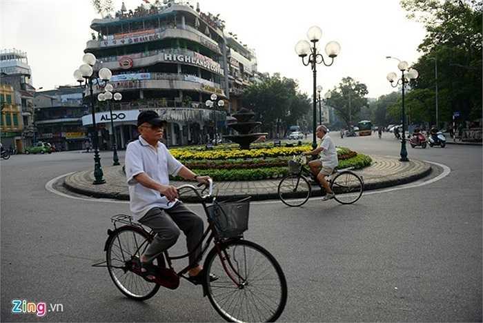 Quảng trường Đông Kinh Nghĩa Thục, các cụ già thảnh thơi đạp xe dạo mát.