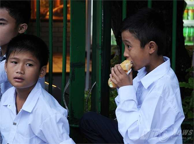 Cậu học sinh tranh thủ ăn bánh mì trong lúc chờ vào Lăng viếng Bác (Tùng Đinh/Thực hiện)