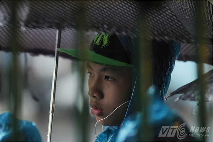 Một cậu bé đội mưa đứng chờ vào viếng Bác