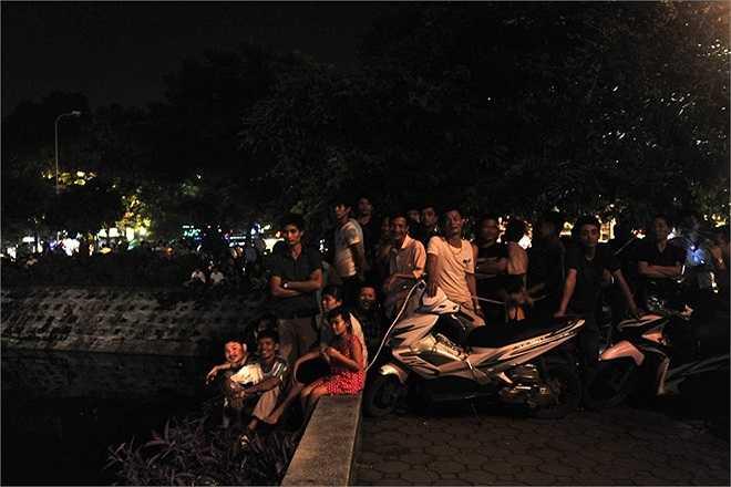 Xung quanh hồ rất đông người dân hiếu kỳ tập trung xem và nghe ngóng tình hình.