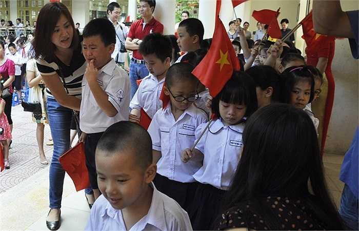 Ra sân chuẩn bị cho lễ chào cờ, nhiều học sinh còn rớm nước mắt, bố mẹ phải luôn đi bên cạnh để động viên. (Ảnh: Minh Chiến)