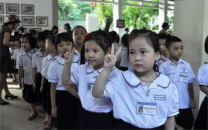 Học sinh lớp 1 tạo dáng chụp hình kỉ niệm trong ngày khai giảng. (Ảnh: Minh Chiến)