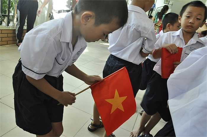 Tú Anh tự sửa lại lá cờ của mình trước giờ khai giảng. (Ảnh: Minh Chiến)