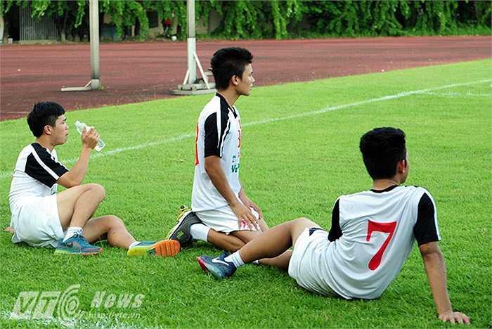 Vừa uống nước, thủ quân của U19 Việt Nam vừa xem các đồng đội tập luyện