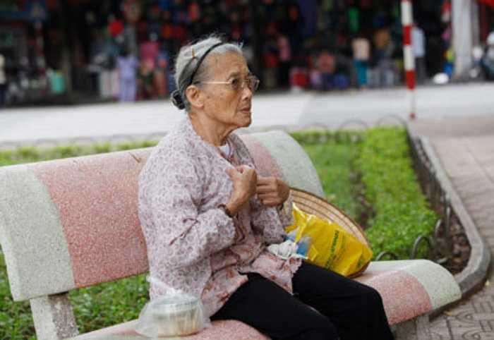 Cụ bà khoác thêm chiếc áo mỏng, ngồi lặng mình trong tiết trời Hà Nội chìm vào cuối mùa thu.