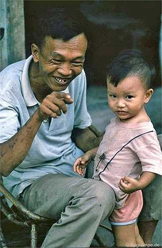 Hai ông cháu cười đùa trên một hè phố, với một con chuồn chuồn trên áo đứa bé chừng hai tuổi.