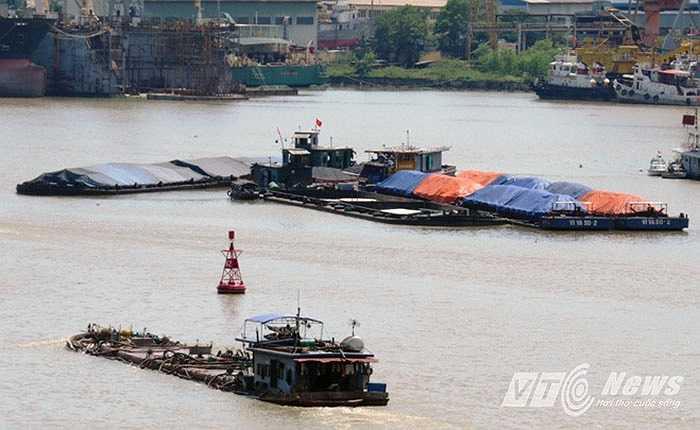 Phía tả, hữu cầu Bính, nhiều phương tiện Thủy chở hàng quá tải trọng đậu đỗ chở bốc hàng.