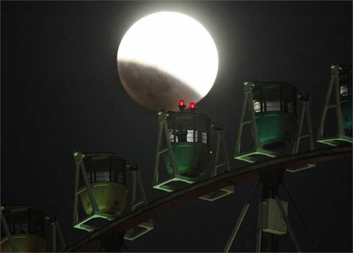Mặt trăng bị che khuất một phần phía sau vòng đu quay Ferris ở Tokyo, Nhật Bản