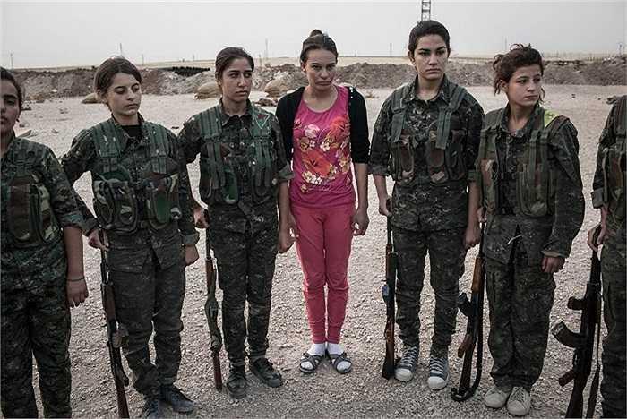 Nữ tân binh mặc bộ quần áo màu hồng trong ngày đầu tiên tham gia buổi huấn luyện tại căn cứ ở Derek, Syria