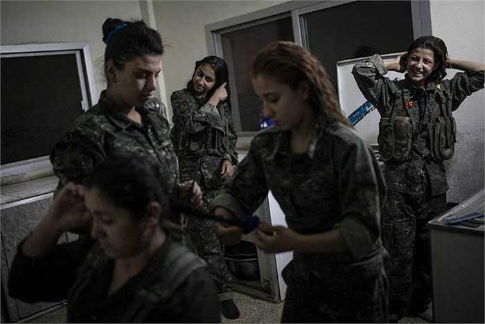 Các nữ chiến binh búi tóc gọn gàng chuẩn bị cho buổi tập huấn vào sáng sớm ở thành phố Derek, Syria