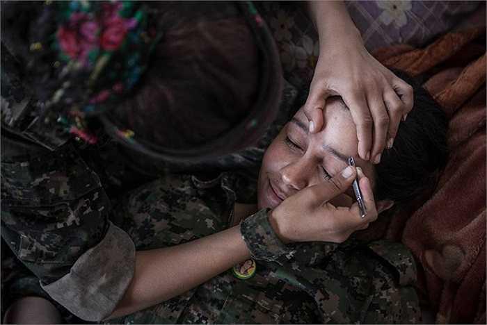Nữ chiến binh Asadi Kamishloo, 22 tuổi, được một đồng đội tỉa lông mày