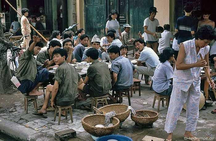 Hàng ăn uống trên hè phố rất nhiều. Thực khách trò truyện rôm rả ngay bên những rổ bát bám đầy ruồi nhặng.