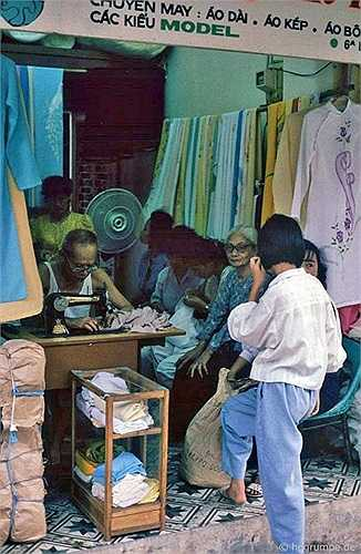 Trong hiệu may áo dài, bác thợ may đang đạp máy khâu trong lúc các vị nữ khách bình thản ngồi đợi.
