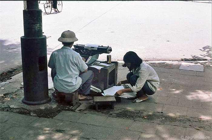 Đánh máy chữ thuê là công việc của người đàn ông này tại vỉa hè gần Bưu điện Bờ Hồ. Cô con gái nhỏ ngồi đọc văn bản và giúp bố soạn lại những giấy tờ của khách.