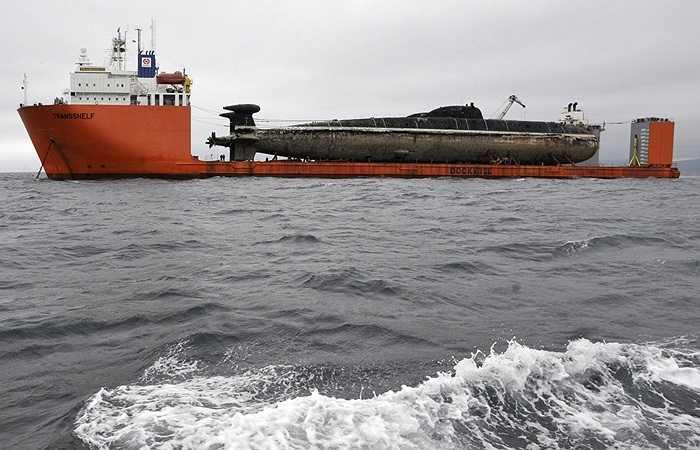 Con tàu ngầm từng kiêu hãnh một thời, nay chỉ còn là cái xác, được đưa lên tàu vận tải siêu trọng của hãng Rolldock Sea, được sử dụng làm tàu mẹ đưa tàu ngầm đến nơi tháo dỡ. Trong đó quan trọng nhất là xử lý lò phản ứng hạt nhân.