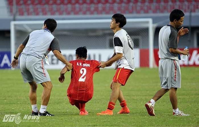 Trợ lý HLV và đồng đội vào sân kéo Văn Sơn đứng lên.