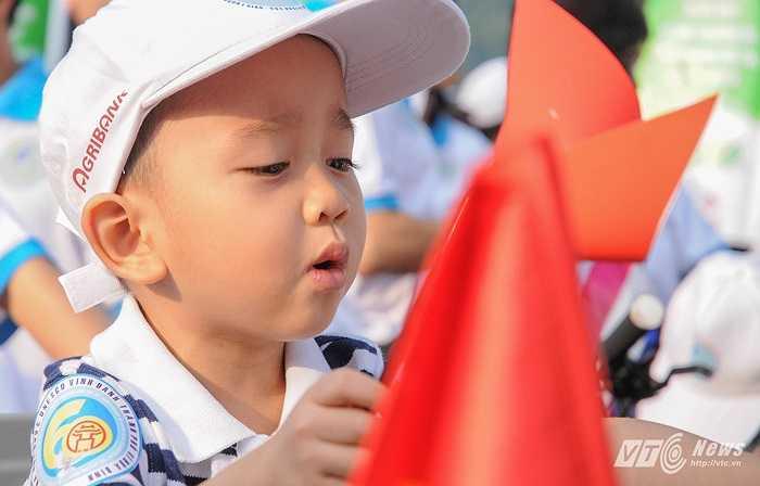Em bé ngồi sau xe của bố nghịch chong chóng giấy trước giờ xuất hành
