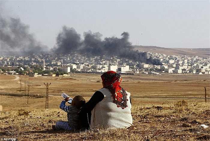 Người dân địa phương ngồi xem các cuộc không kích của Mỹ