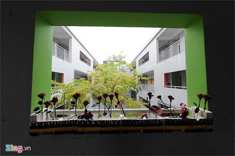 Một góc nhà trường nhìn từ cửa sổ có nhiều hoa do học sinh tự tay làm.