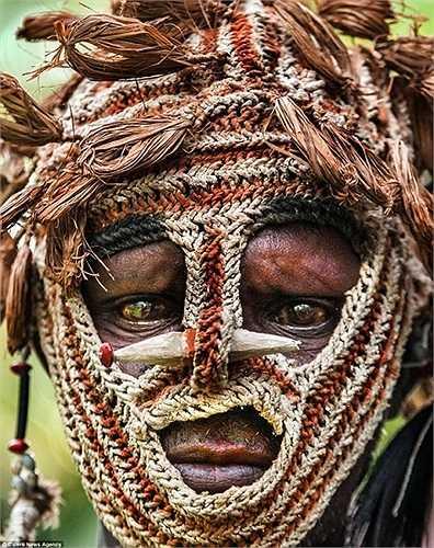 Một chiến binh bộ tộc Asmat đeo mặt nạn chiến đấu trên đảo New Guinea, Indonesia