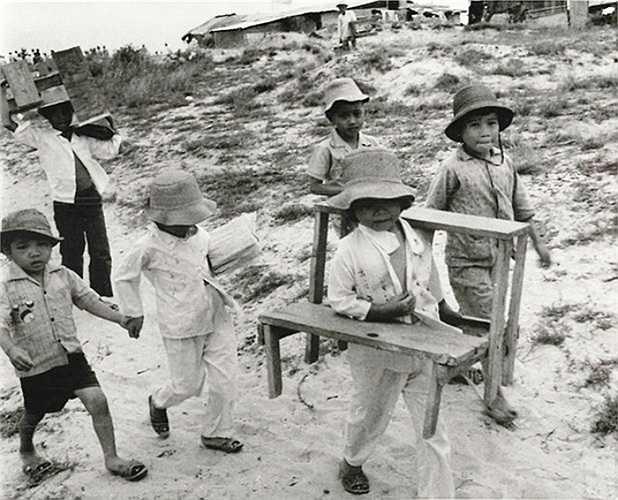 Các học sinh nhỏ bê bàn ghế đến lớp học ngoài trời của mình ở Quảng Trị, ngày 24/9/1973. Trường của các em đã bị phá hủy trong chiến sự năm 1972.