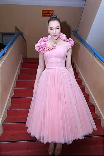 Trái ngược với váy đen của Hồ Ngọc Hà, Hồ Quỳnh Hương diện bộ đầm có gam hồng. Phần vai được thiết kế như một lẵng hoa, khiến nữ ca sĩ trông vừa dịu dàng vừa gợi cảm.