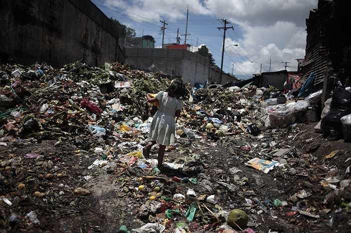 Cô bé này đang đi qua bãi rác do chợ thức phẩm La Terminal thải ra ở thành phố Guatemala.