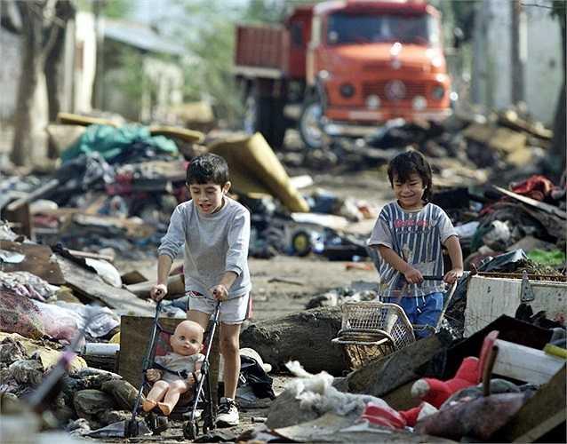 Đôi bạn nhỏ đi qua những đống rác trên đường phố ở Santa Fe, Argentina.