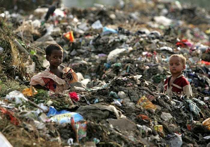 Những đứa trẻ như 'chìm' trong biển rác ngoại ô New Delhi, Ấn Độ.