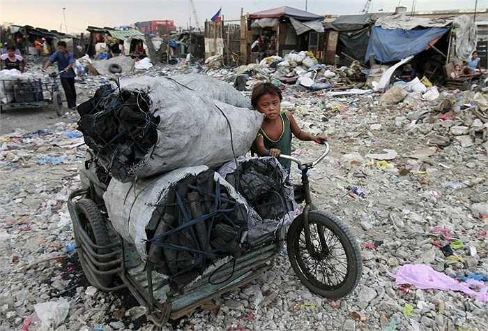 Cậu bé đẩy xe chất đầy than củi, đi qua một bãi rác.