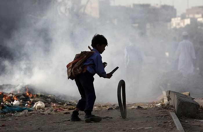 Rác trở thành đồ chơi cho cậu bé này. Hình ảnh được chụp ở Karachi, Pakistan.