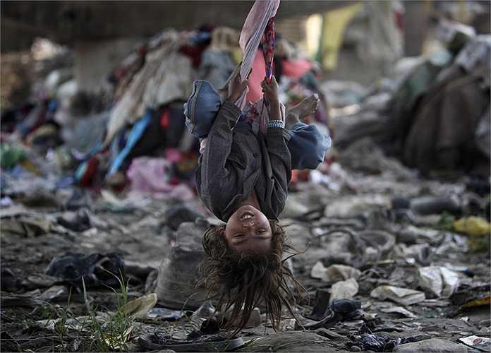 Một em bé nhún đu dưới cây cầu giữa một bãi rác ở Kathmandu, Nepal.