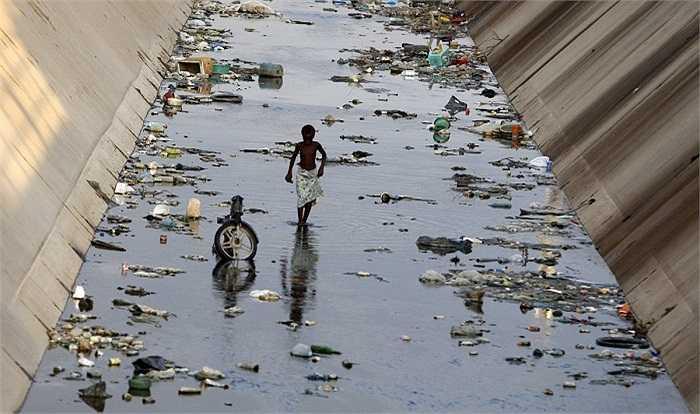 Những bức ảnh cho chúng ta thấy cách mà thế hệ trẻ buộc phải thích ứng với một hành tinh ô nhiễm và đầy rác.Cậu bé này đang đi qua một con kênh ô nhiễm ở Benguela, Angola.