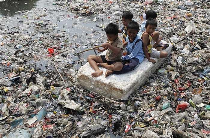 Dòng sông chứa đầy rác thải ở Jakarta, Indonesia lại trở thành nơi thám hiểm cho những em bé hiếu kỳ này.