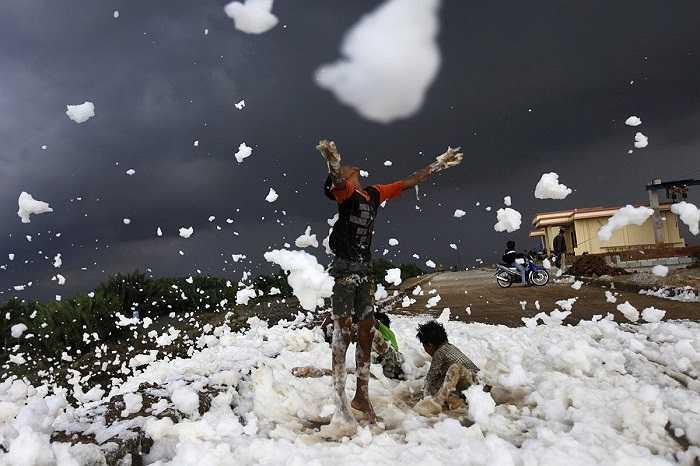 Những đứa trẻ chơi trên dòng sông ô nhiễm, nổi bọt trắng xóa ở Jakarta, Indonesia.