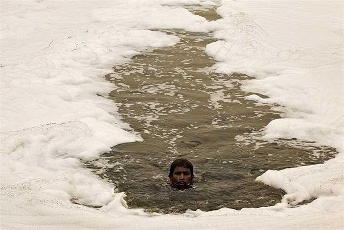 Giá như đây là dòng nước trong xanh để em tha hồ vẫy vùng. Cậu bé này đang bơi qua dòng sông đầy bùn bẩn Yamuna ở New Delhi, Ấn Độ.