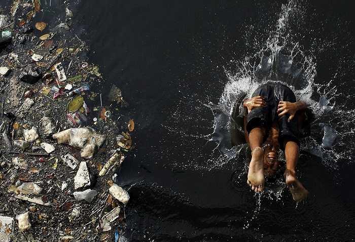 Hình ảnh cậu bé làm cú lộn nhào xuống dòng nước đen ngòm, bên cạnh bãi rác ở Jakarta, Indonesia.