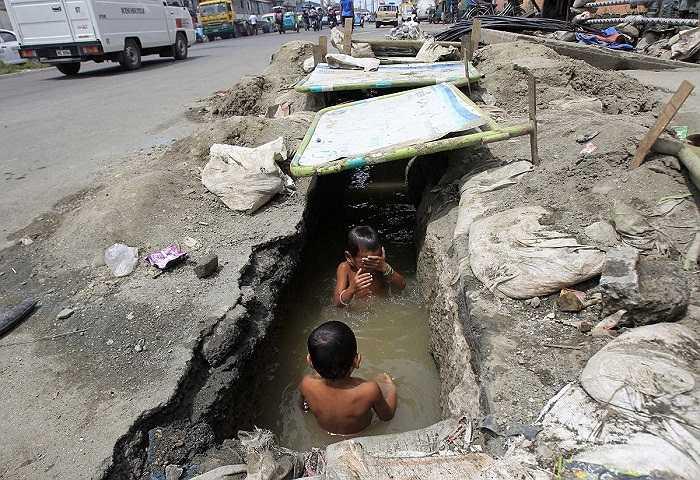 Một con mương thoát nước nghiễm nhiên trở thành bể bơi cho 2 em bé này. Hình ảnh được ghi lại ở Manila, Philippines.