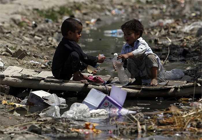 Hai cậu bé 'chia nhau' chai nước bẩn bên cạnh vũng nước ô nhiễm, đầy rác thải (Kabul, Afghanistan).