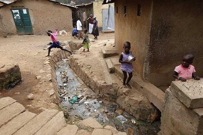 Sống chung với rác và nước ô nhiễm (Kampala, Uganda). Cống rãnh không có nắp đậy ngay trước cửa nhà dân.