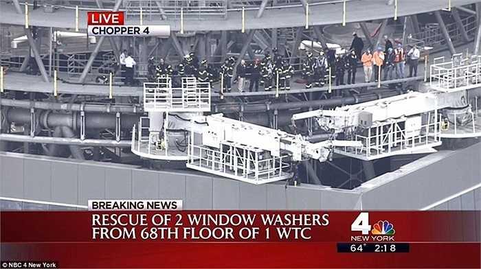 Các nhân viên cứu hộ có mặt trên nóc tòa nhà để giữ cho giàn giáo không rơi xuống