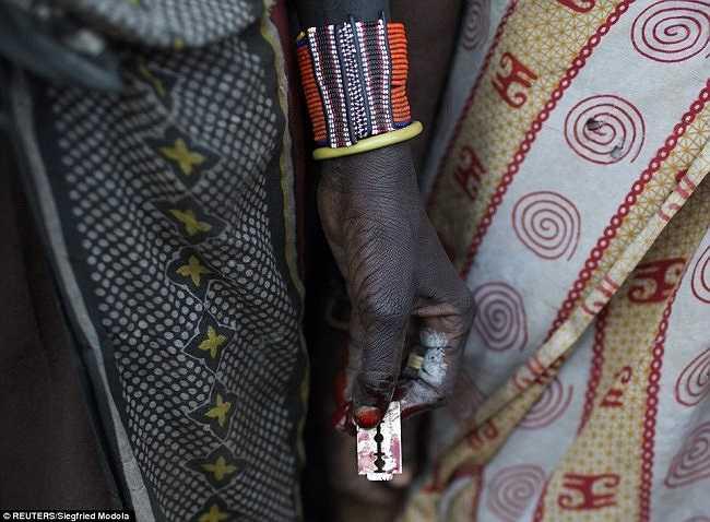 Một người phụ nữ Pokot giữ lưỡi dao cạo sau khi thực hiện cắt bao quy đầu cho bốn cô gái.