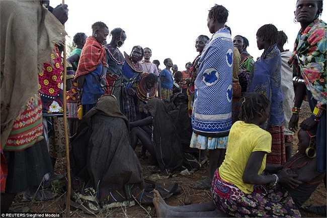 Các cô gái được bao phủ bởi da thú, ngồi xổm trên đá sau khi bị lột và tắm rửa sạch trong nghi lễ cắt bao quy đầu của họ.