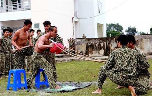 Một chiến sĩ đặc công thể hiện khả năng phi thường, khi cổ họng ghì cong 3 cây giáo nhọn, vai kê gạch để đồng đội công phá