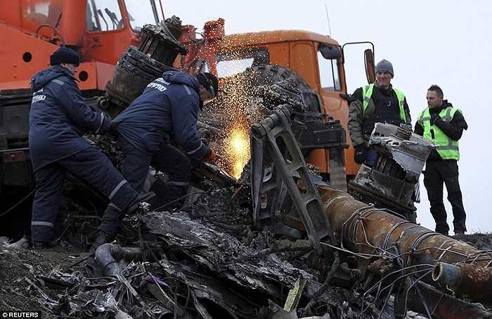 Các công nhân địa phương dùng máy cắt các mảnh vỡ tại hiện trường thảm họa