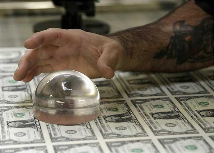 Kỹ thuật viên dùng kính lúp kiểm tra các tờ tiền sau khi in