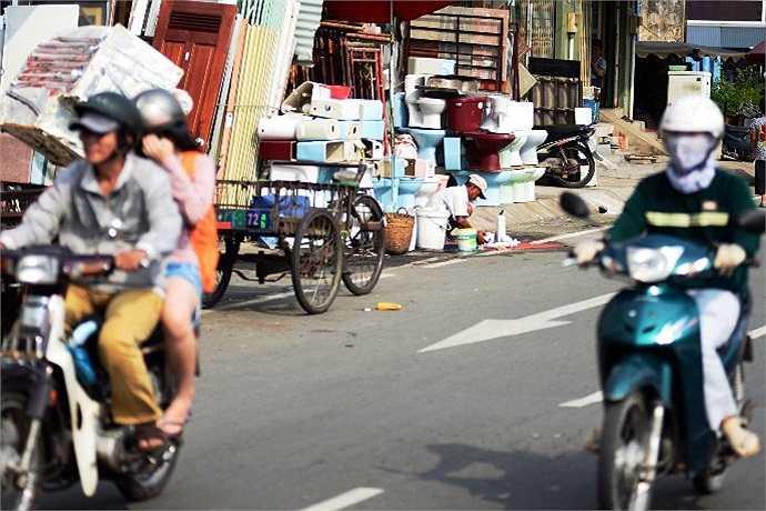 Cảnh buôn bán hàng rong rửa chén, đổ nước tràn lan ra đường. (Ảnh Quang Hưng)