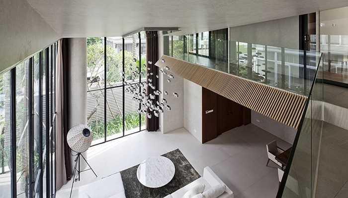Không gian phòng khách nhìn từ trên cao xuống. Hành lang tầng 2 được làm che chắn bằng vách kính trong suốt, hiện đại.