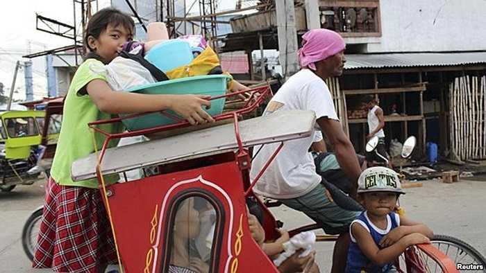 Người lớn, trẻ nhỏ chen chúc nhau trên những chiếc xe ba bánh đến nơi an toàn