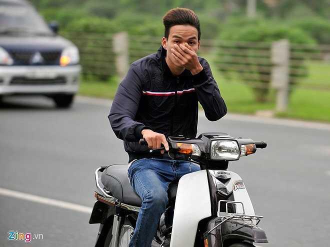 Nam thanh niên không đội mũ bảo hiểm vội vàng che mặt khi bị chụp ảnh đi vào làn ôtô với tốc độ cao